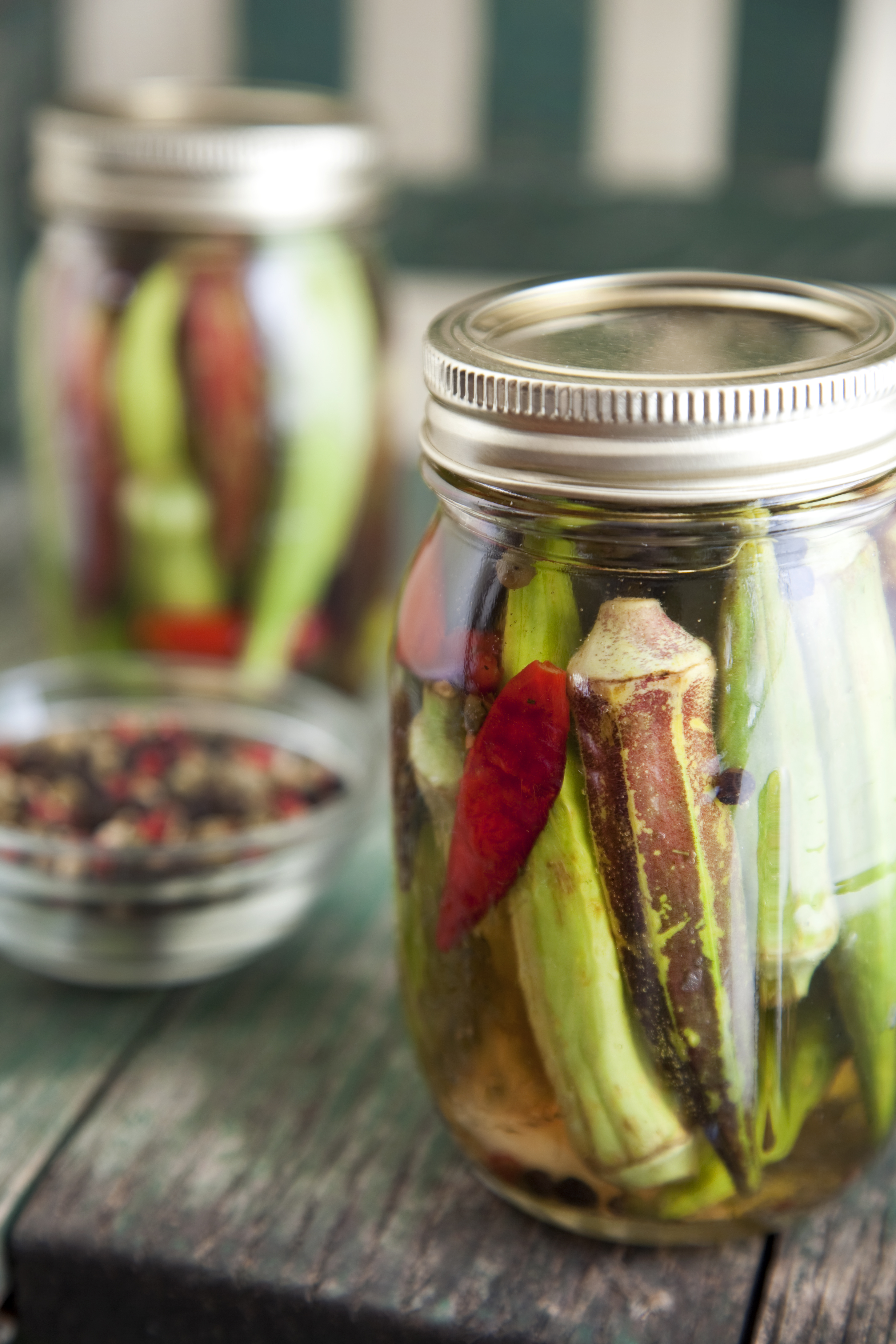 Two jars of pickled okra rest on a primitive country chair.