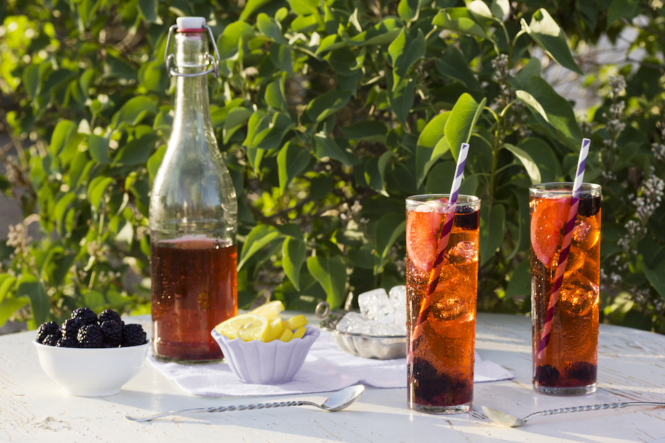 A pitcher of blackberry iced tea and two glasses sit on a wooden table in the garden. Lemon wedges and fresh blackberries are on the side.