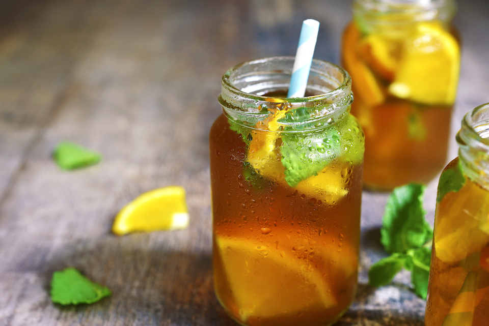 Orange iced tea in a glass jar with paper straws on a rustic wooden background.