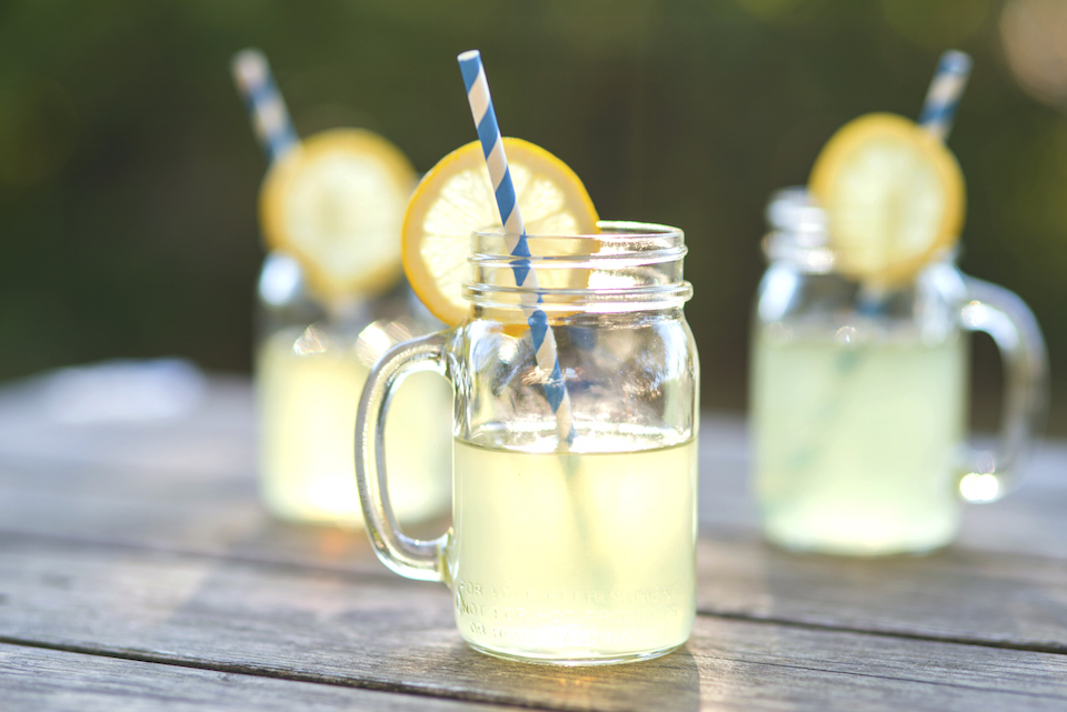 Lemonade glass jars with lemon wedges and straws sitting on a wood tabletop