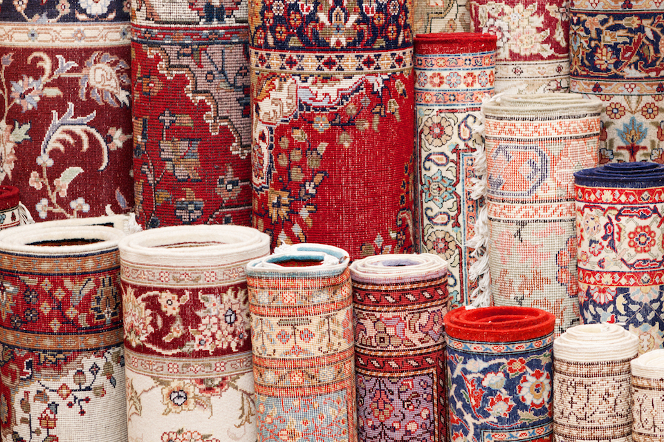 Close up of various handmade Persian carpets in a shop