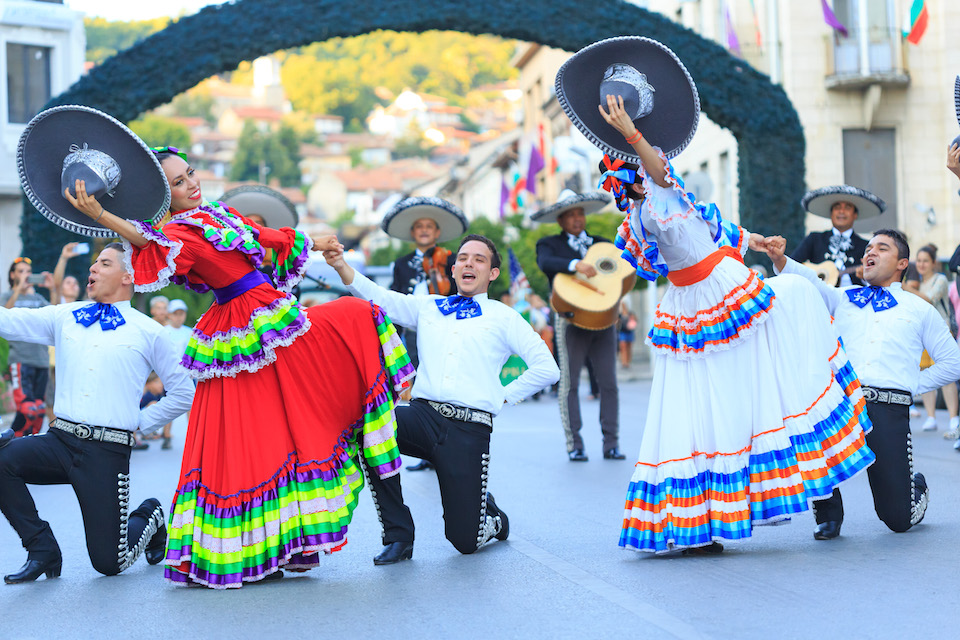 """Veliko Tarnovo, Bulgaria- July 25, 2015: Mexican men and women from a folklore group for traditional dances kneeling on street in final position during a parade of """"International Folklore Festival Veliko Tarnovo"""", Bulgaria. The festival is a prestigious folklore event which became significant and traditional part of the cultural life of the ancient capital of Bulgaria. A real long – expected holiday for habitants and guests of the city in the hot summer days. Today, Veliko Tarnovo is the center of one of the largest urban areas in Bulgaria."""