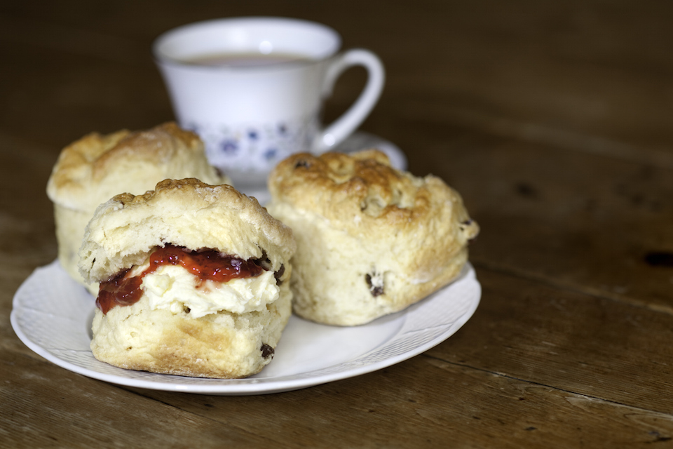 Delicious scones, cream and jam on a wooden table
