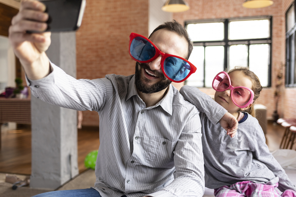 Father and daughter with funny sunglasses taking selfie at home