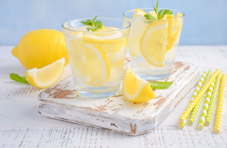 Cold refreshing summer drinks with lemon and mint on wooden background.