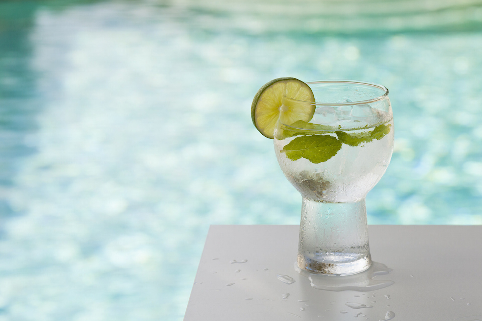 Glass of iced water with lime and mint garnish resting on a table in front of crystal-blue pool water in Dallas, Texas.
