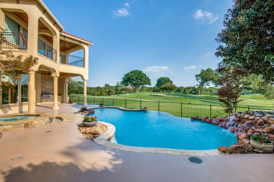 Backyard infinity pool overlooking golf course at 5600 Wayfarer Drive in Plano, Texas.