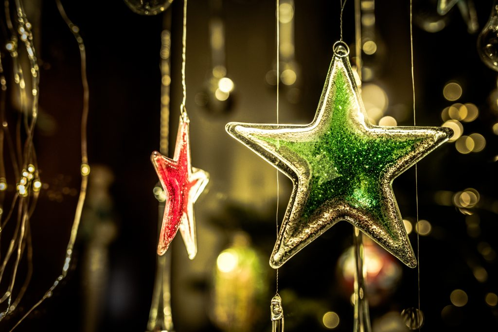 Christmas Star are hanging in storefront at night.