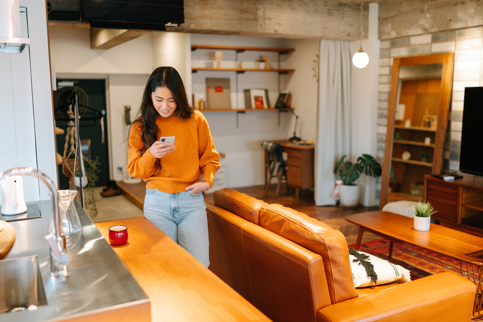 Woman at home using smartphone